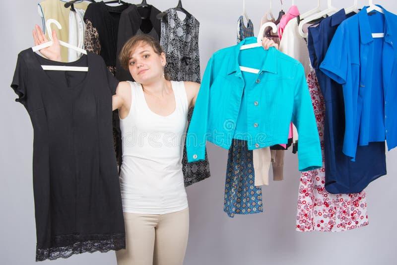 La ragazza non ha conosciuto che cosa scegliere dai vestiti nel guardaroba fotografia stock