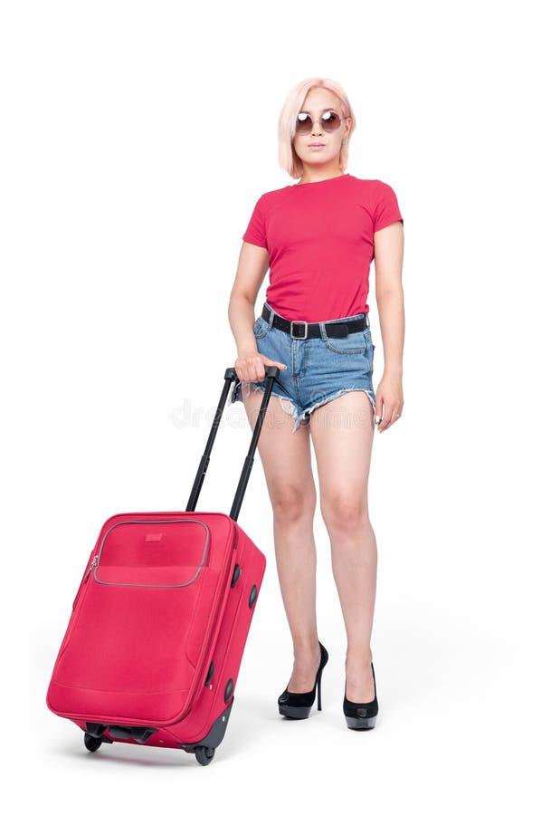La ragazza in occhiali da sole, mette e supporti rosa della maglietta con una valigia, isolata su fondo bianco immagine stock libera da diritti