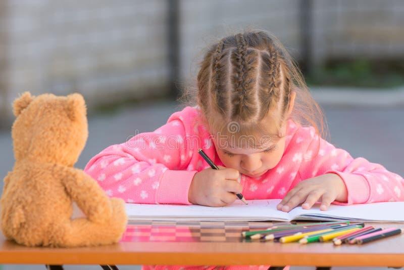 La ragazza offensiva disegna una figura hunched nell'iarda fotografia stock