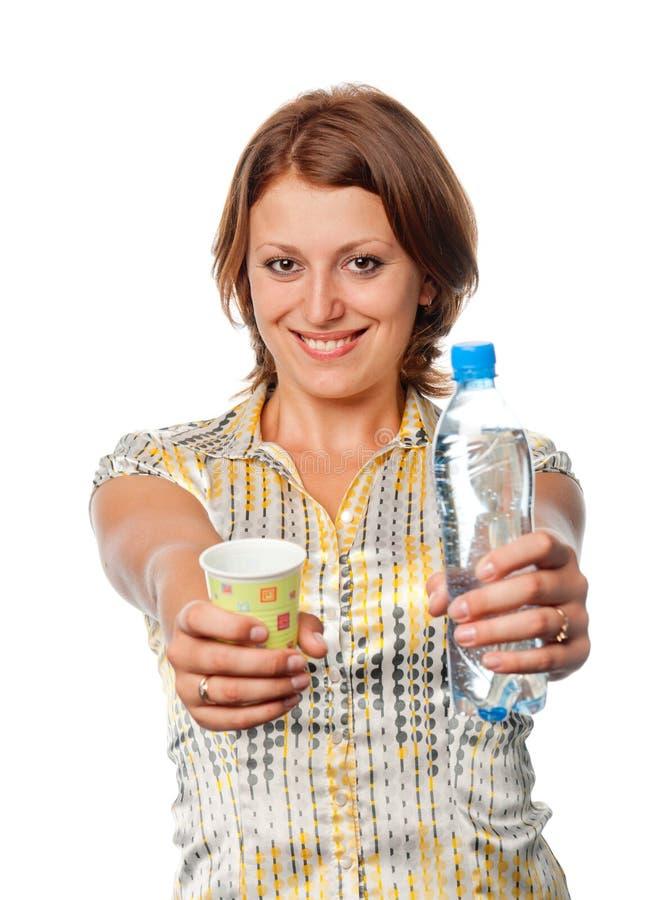 La ragazza offre una bottiglia dell'acqua e di un vetro fotografie stock libere da diritti