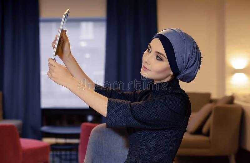La ragazza orientale affascinante in vestiti musulmani fa il selfie su gadge elettronico fotografia stock libera da diritti