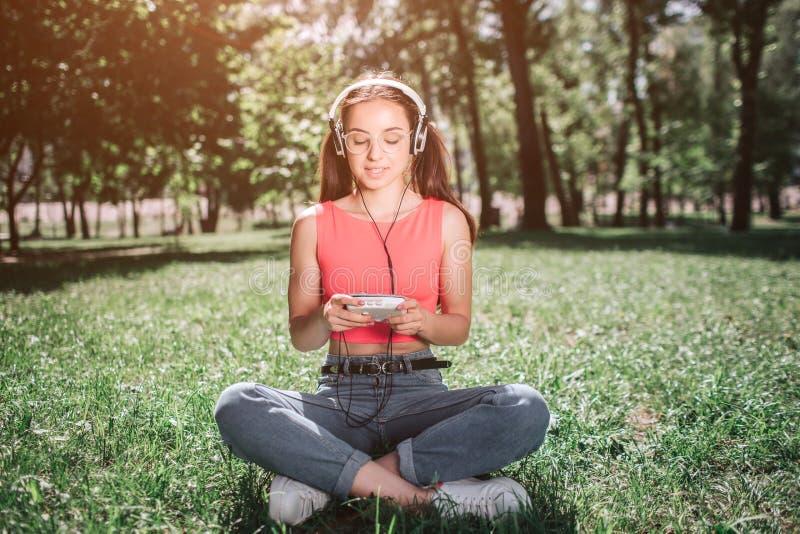 La ragazza pacifica e rilassata sta sedendosi sull'erba con le sue gambe attraversate e sta ascoltando musica Ha cuffie lei immagine stock libera da diritti