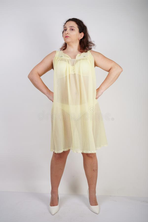 La ragazza paffuta graziosa che porta la biancheria intima gialla alla moda ed ama il suoi corpo e donna grassottella in biancher fotografie stock libere da diritti