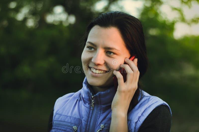 La ragazza parla sul telefono all'aperto immagine stock