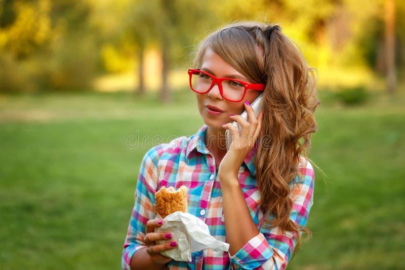 La ragazza parla sul telefono e sulla tenuta del hot dog fotografia stock libera da diritti