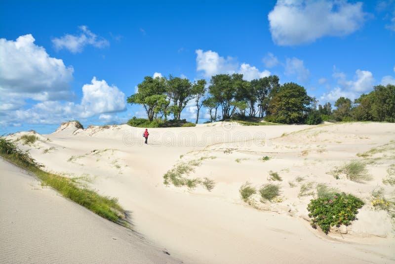 La ragazza passa attraverso le dune di sabbia pittoresche fotografie stock