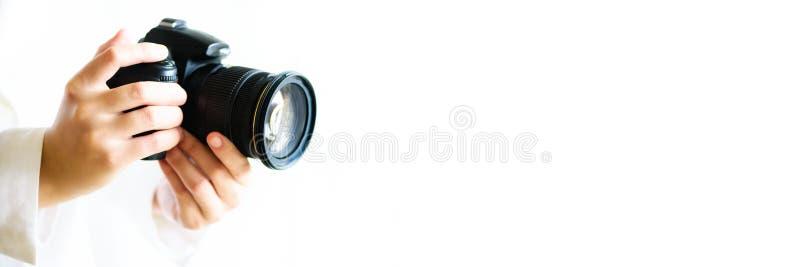 La ragazza passa la macchina fotografica della foto della tenuta, fondo bianco, spazio della copia Viaggio e concetto del tiro ba immagini stock