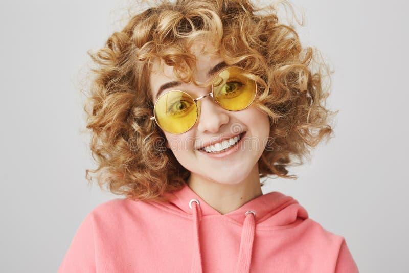 La ragazza pazza attraente non si siede mai a casa il fine settimana Ritratto della donna riccio-dai capelli felice divertente in immagini stock