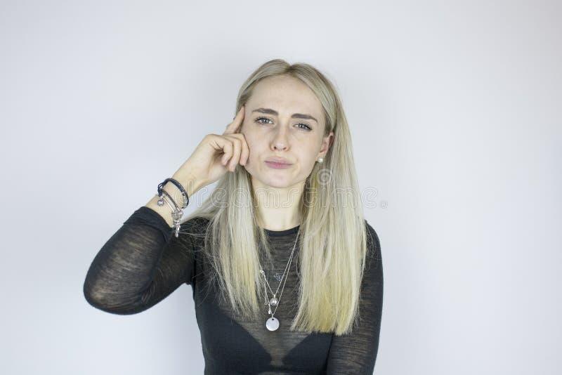 La ragazza pensa e cerca, tenendo un dito vicino alla testa fotografie stock libere da diritti