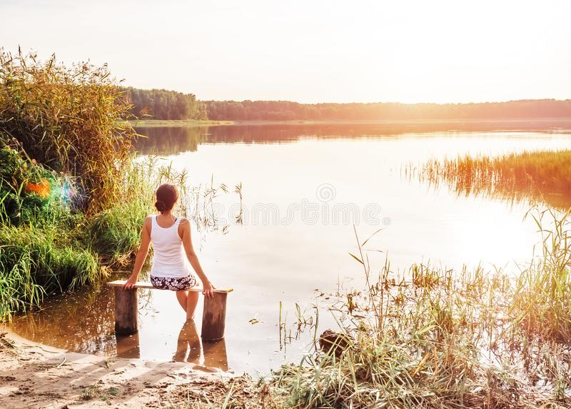 La ragazza pensierosa si siede su un banco dal fiume e gode di bello tramonto Ragazza che si siede vicino all'acqua all'aperto Tr fotografie stock libere da diritti