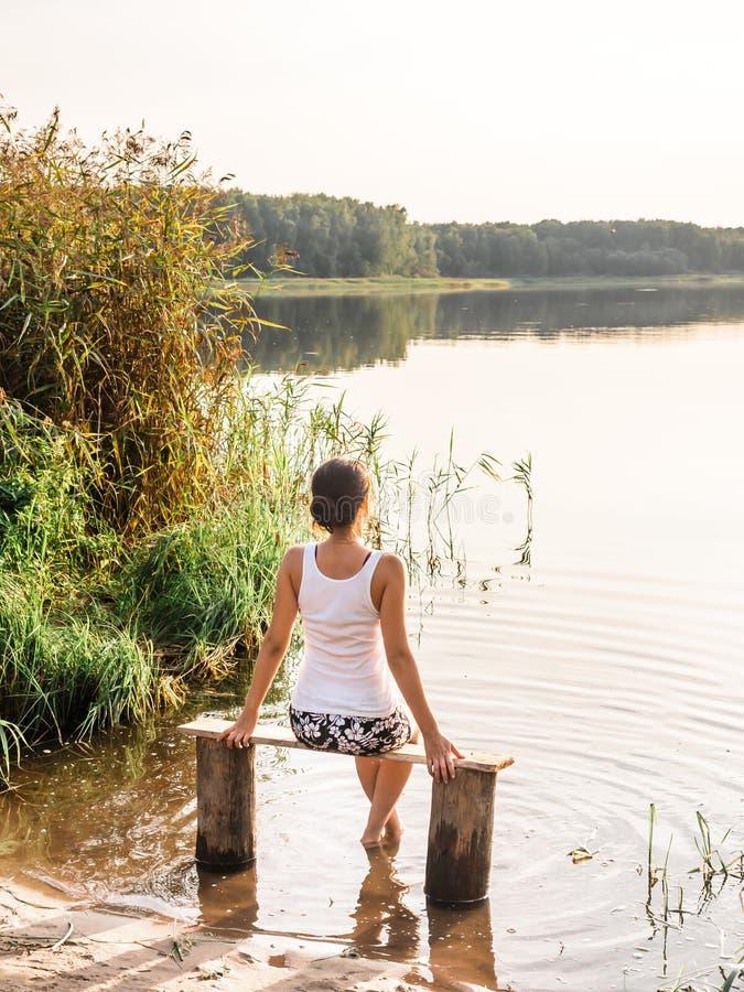 La ragazza pensierosa si siede su un banco dal fiume e gode di bello tramonto Ragazza che si siede vicino all'acqua all'aperto Tr immagini stock libere da diritti