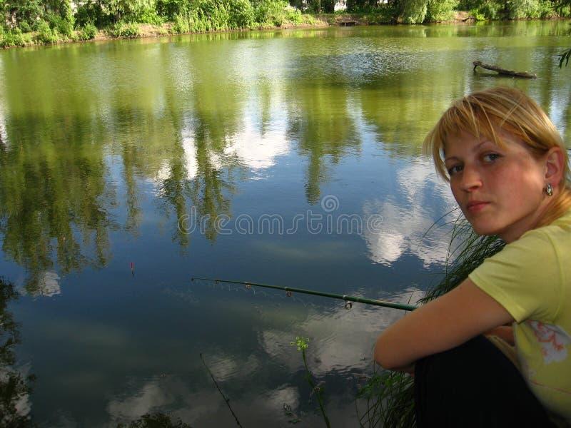La ragazza pesca un pesce fotografie stock