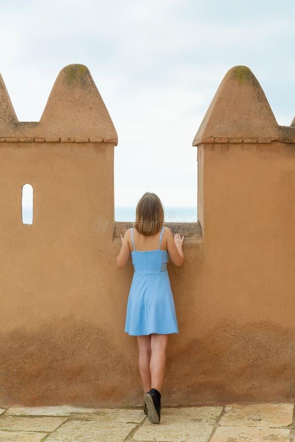 La ragazza piacevole considera la città dalla fortezza medievale immagine stock
