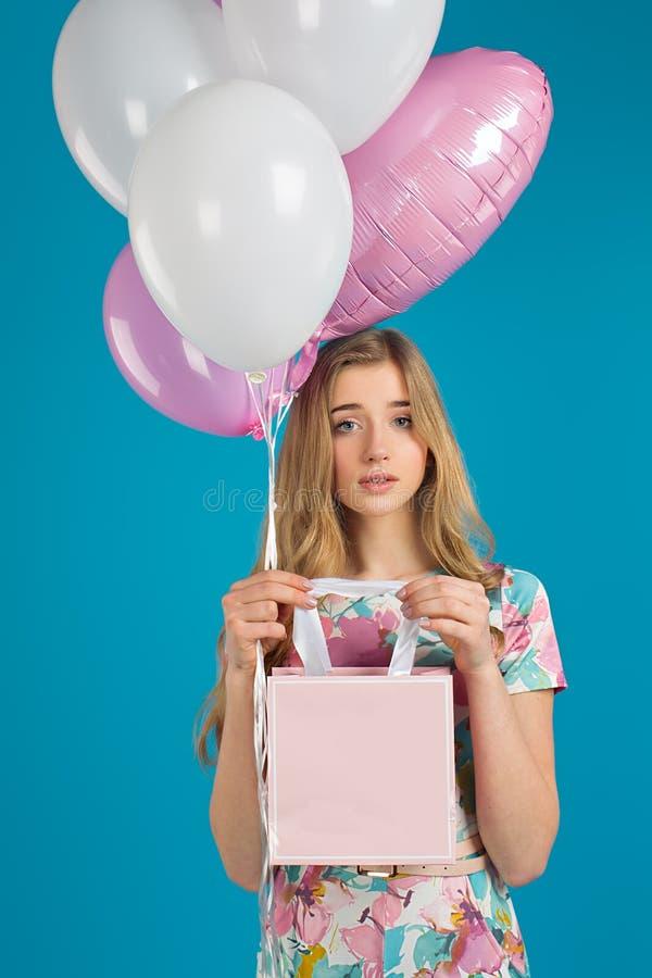 La ragazza piacevole dolce con i baloons ed i piccoli prersents insaccano nelle mani sui precedenti blu Umore della sorgente fotografie stock