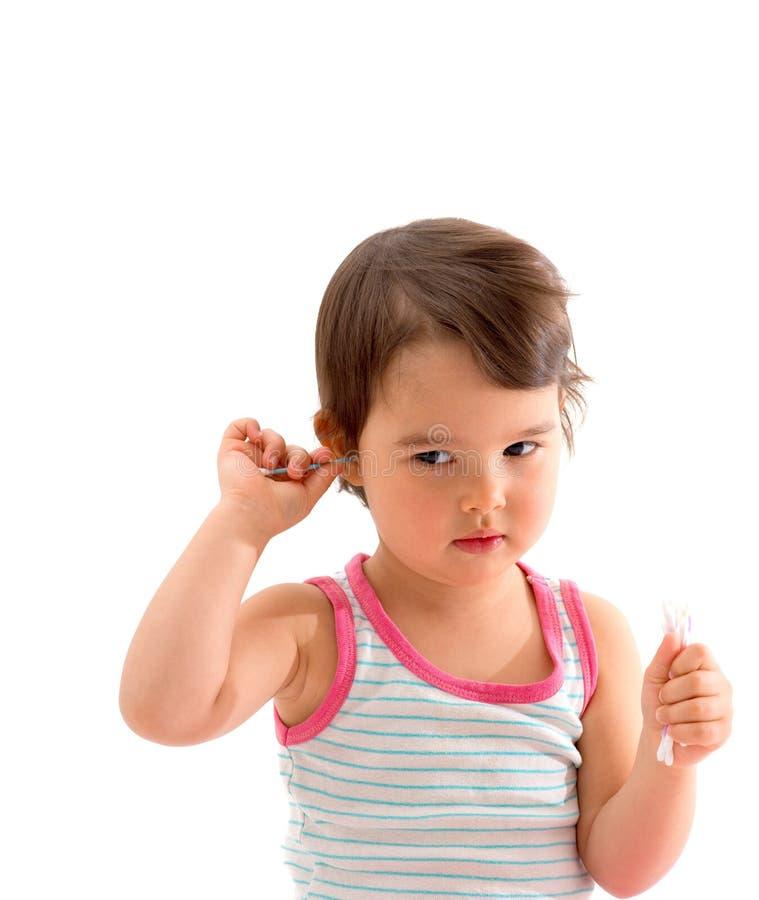 La ragazza in pigiami pulisce le Q-punte delle orecchie immagini stock