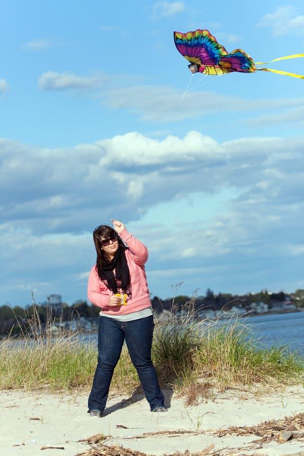 La ragazza pilota un cervo volante al puntello di mare immagini stock libere da diritti