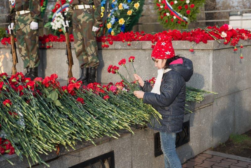 La ragazza pone i fiori rossi del garofano su Victory Memorial durante la celebrazione di Victory Day fotografie stock