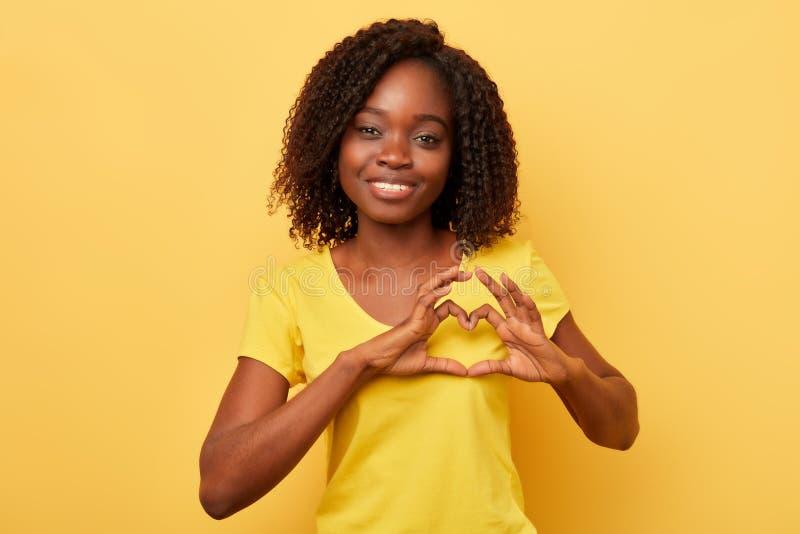 La ragazza positiva incantante con capelli ricci esprime il suo amore, sensibilità calda fotografia stock libera da diritti
