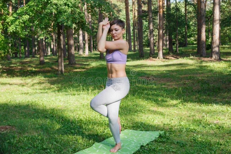 La ragazza pratica l'yoga nel parco un giorno soleggiato fotografia stock