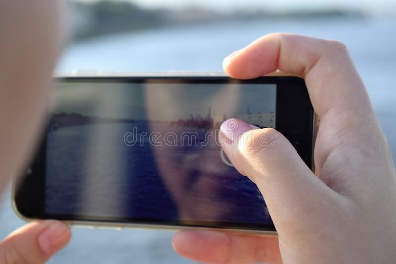 La ragazza prende le immagini sullo smartphone fotografie stock
