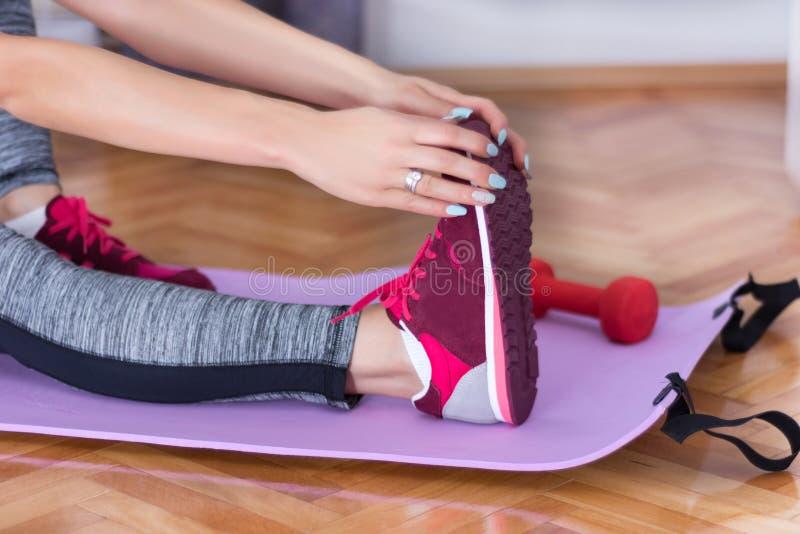 La ragazza prepara la gamba con le scarpe da tennis rosse a casa sulla stuoia porpora di forma fisica o di yoga fotografia stock