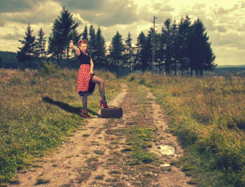 La ragazza prova a andare autostoppista che sta su una strada rurale immagine stock