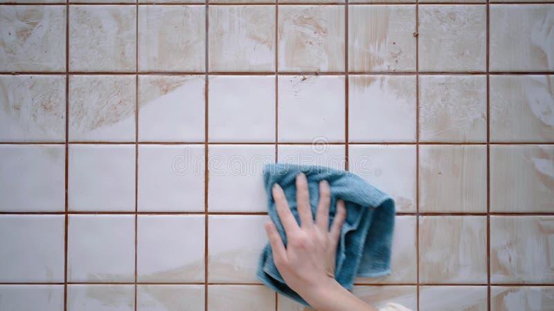 La ragazza pulisce le piastrelle di ceramica sul tavolo da cucina