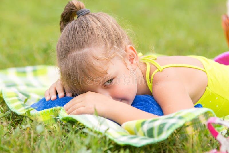 La ragazza quinquennale si trova su un letto sul prato verde ed astuto guarda da parte fotografie stock libere da diritti