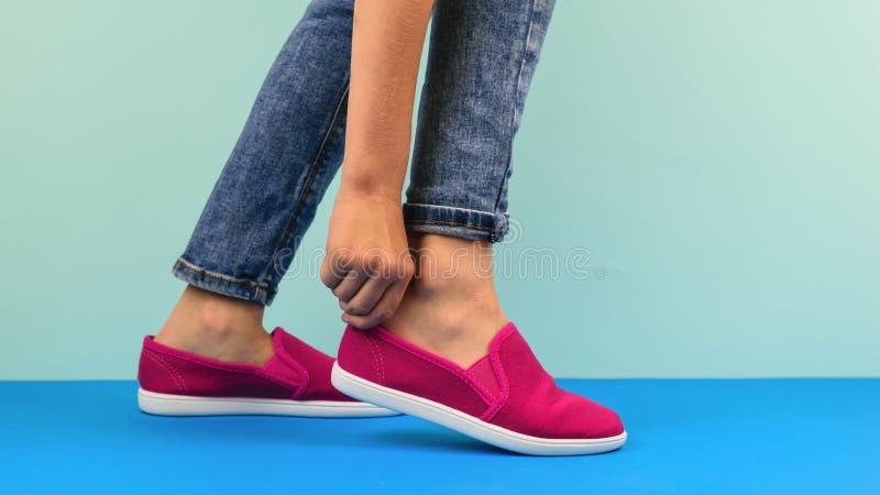 La ragazza raddrizza le scarpe da tennis giuste su un pavimento blu fotografia stock libera da diritti