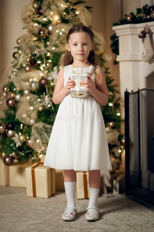 La ragazza in regali della tenuta del vestito si avvicina all'albero di Natale fotografie stock libere da diritti