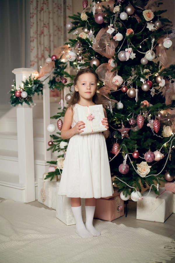 La ragazza in regali della tenuta del vestito si avvicina all'albero di Natale fotografia stock libera da diritti