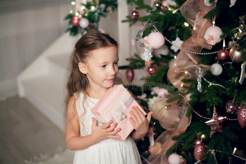 La ragazza in regali della tenuta del vestito si avvicina all'albero di Natale fotografie stock