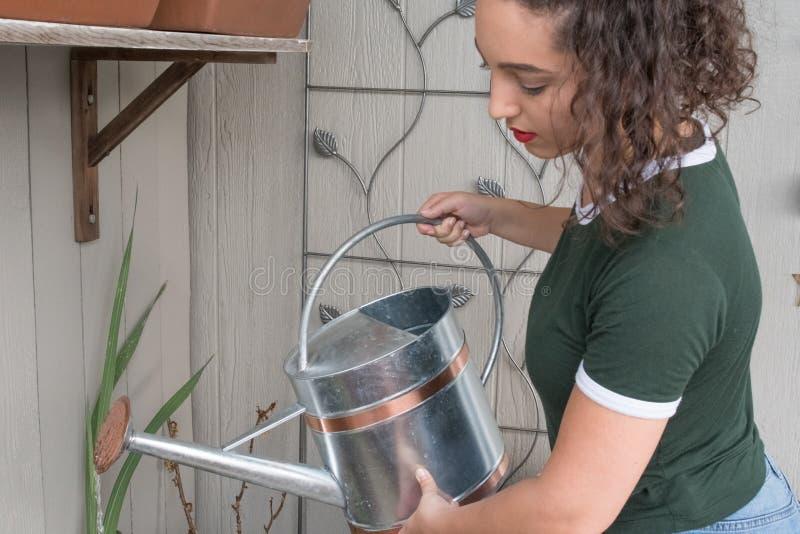 La ragazza ribalta leggermente per versare l'acqua sul giardino immagine stock