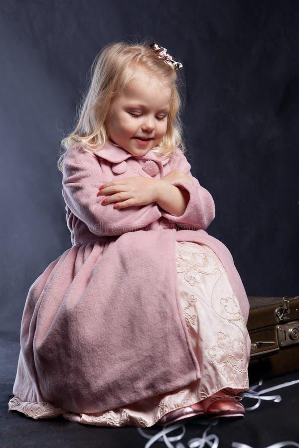 La ragazza riccia in cappotto dentellare si siede in vecchia valigia fotografia stock libera da diritti