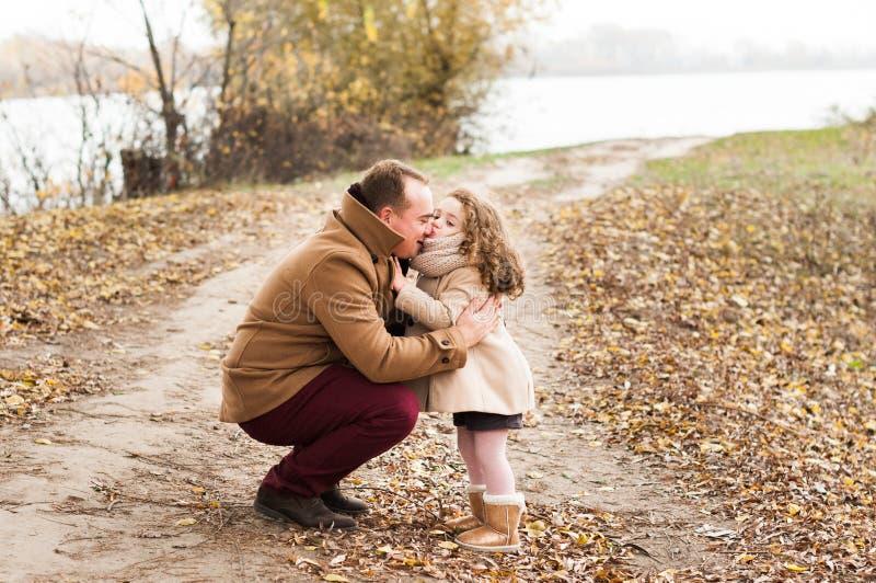 La ragazza riccia divertente bacia il papà immagini stock libere da diritti