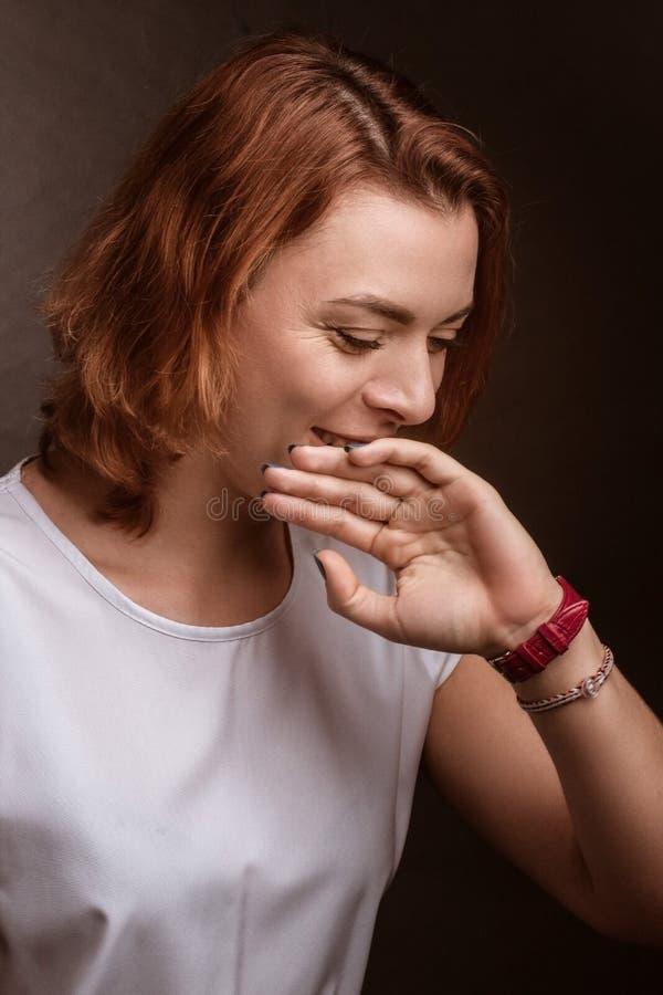 La ragazza ride, si copre la mano con le labbra immagini stock