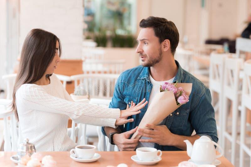 La ragazza rifiuta i fiori, che dà ad un tipo fotografie stock libere da diritti