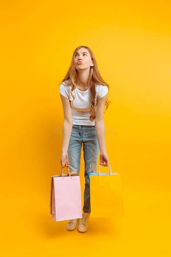La ragazza ritiene stanca da acquisto, una donna con i lotti delle borse, bella ragazza che tiene le borse su un fondo giallo immagini stock