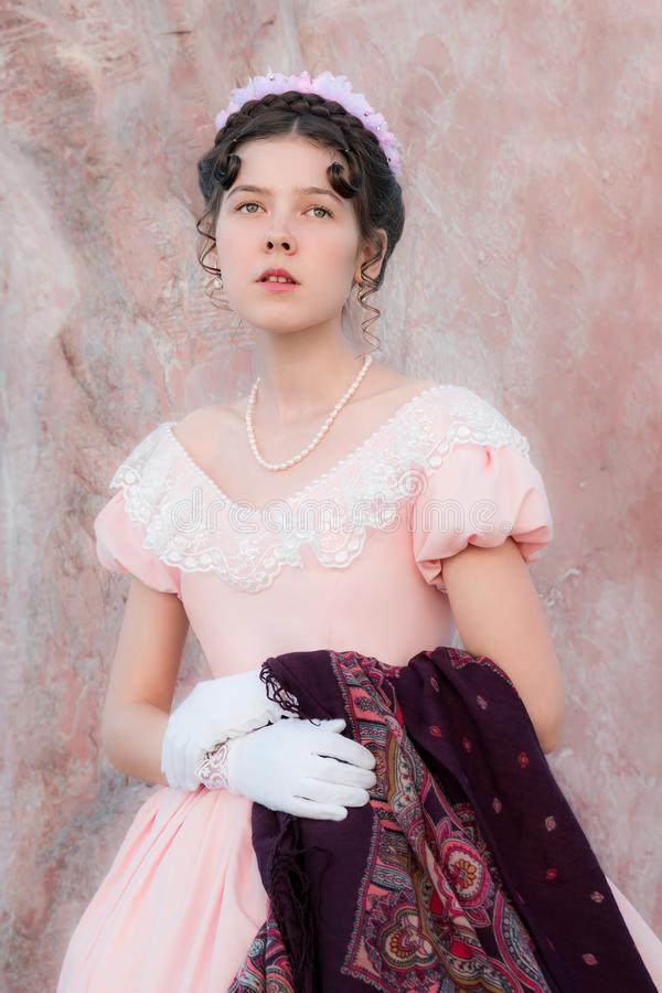 La ragazza romantica in un vestito da sera sta vicino ad una parete dello sto rosa immagini stock
