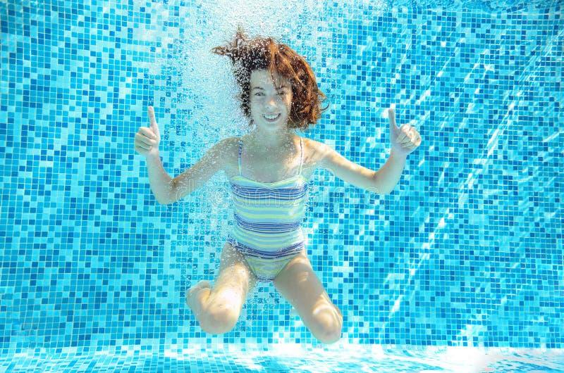 La ragazza salta, si tuffa e nuota in stagno subacqueo, bambino attivo felice si diverte sotto l'acqua, sport del bambino fotografie stock