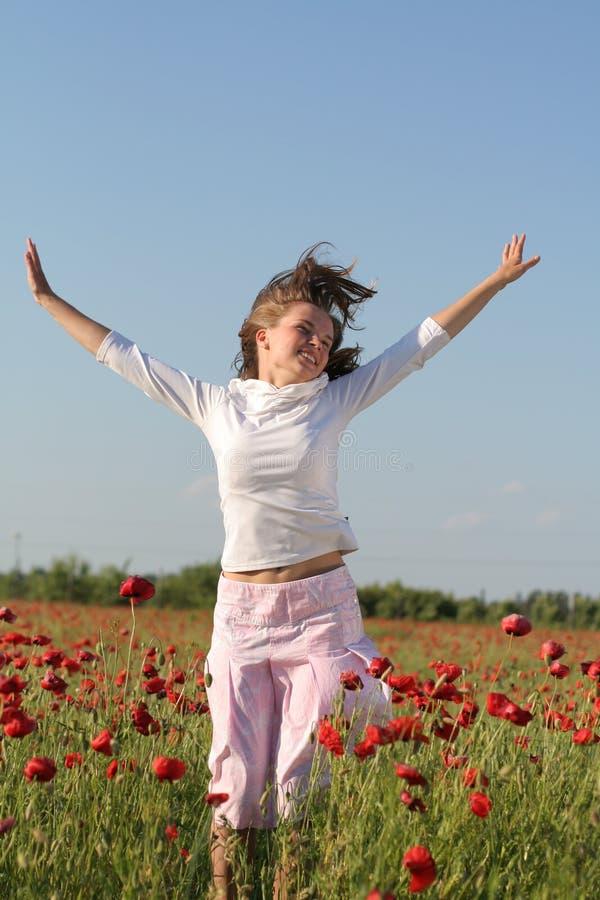 La ragazza salta sopra il campo del papavero fotografia stock libera da diritti