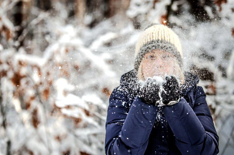La ragazza scarica la neve dalle mani fotografia stock