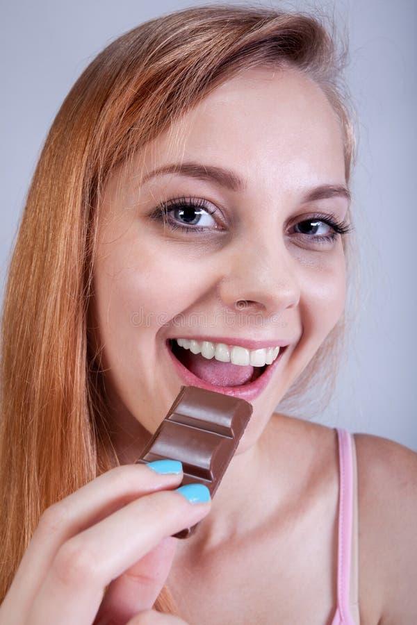 La ragazza scarna mangia i dolci fotografie stock