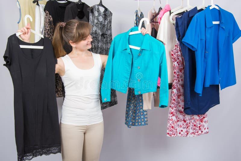 La ragazza sceglie i vestiti il suo guardaroba fotografia stock