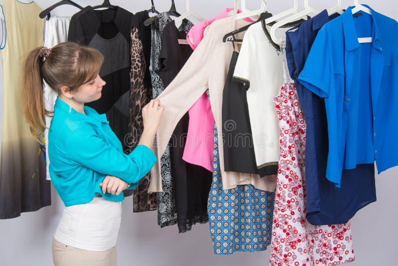 La ragazza sceglie meditatamente i vestiti in guardaroba fotografia stock libera da diritti