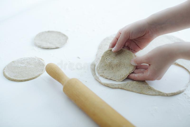 La ragazza scolpisce delicatamente le torte di carne primo piano delle mani sulla tavola fotografia stock