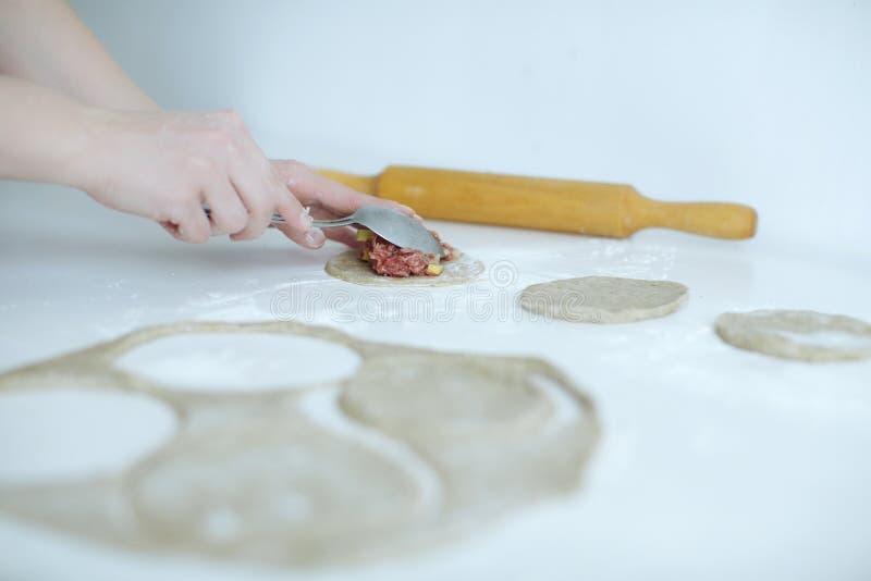 La ragazza scolpisce delicatamente le torte di carne primo piano delle mani sulla tavola con farina immagini stock libere da diritti