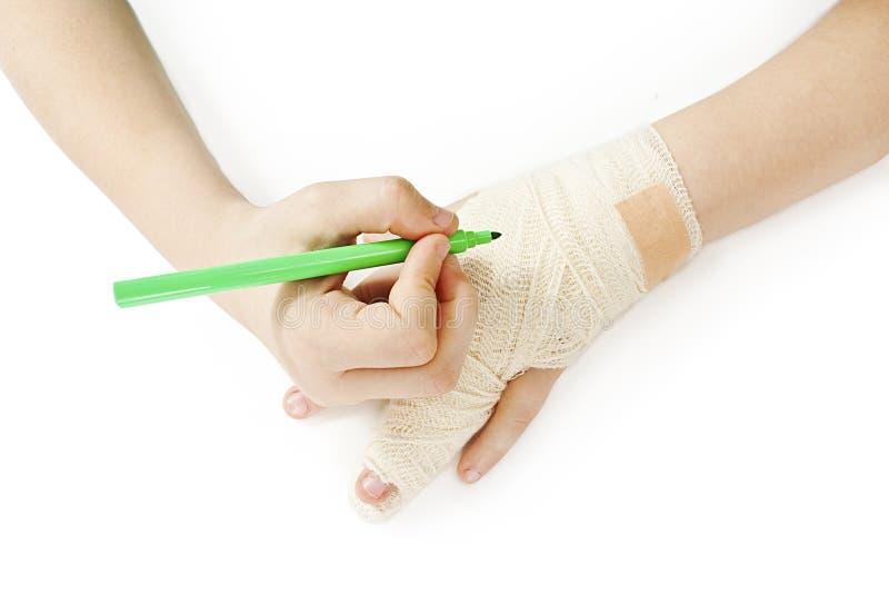 La ragazza scrive con l'indicatore sulla sua mano bendata immagini stock libere da diritti