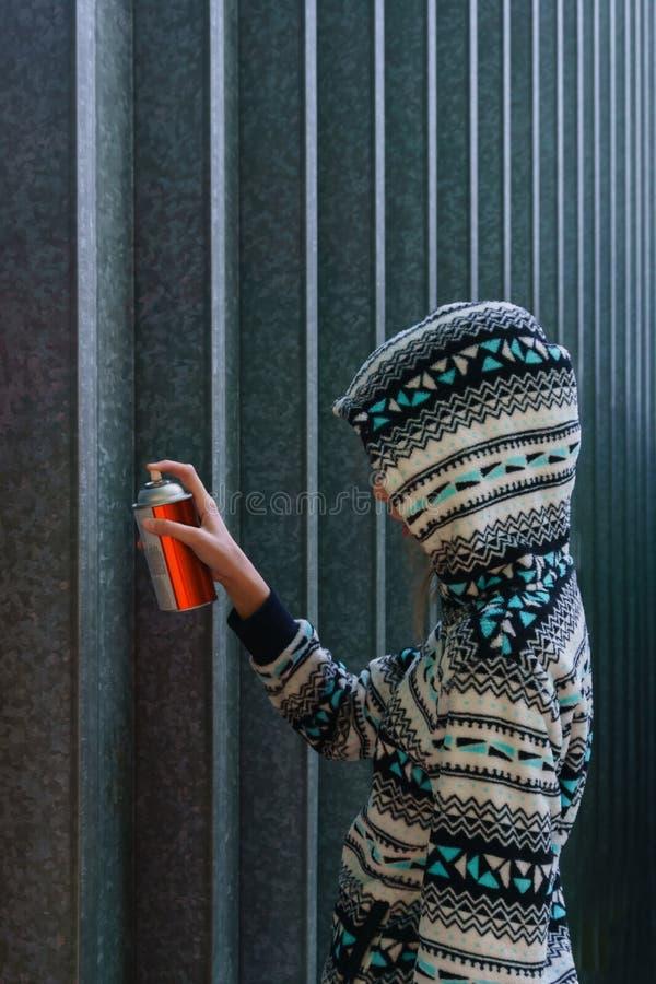La ragazza scrive qualcosa sulla parete immagine stock libera da diritti