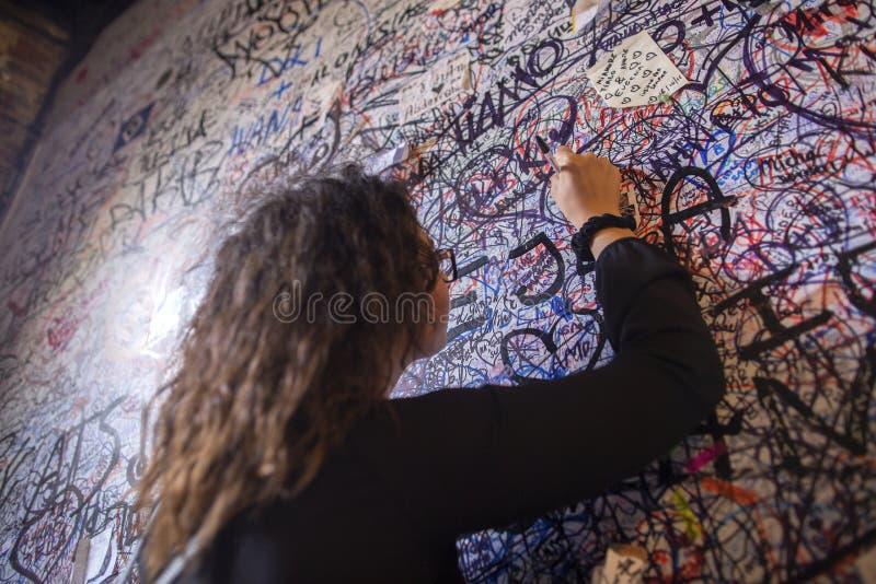 La ragazza scrive un messaggio di amore sulla parete di Juliet Graffiti sulla casa del mattone del Juliet dell'arvicola a Verona  fotografie stock libere da diritti